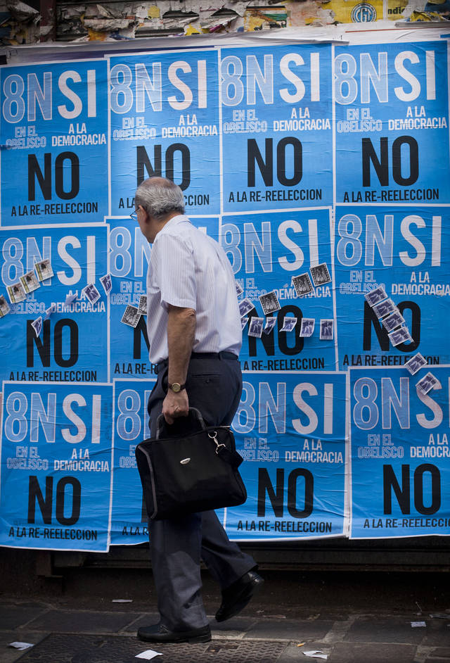 "A man walks by posters promoting an anti-government march in Buenos Aires, Argentina, Wednesday, Nov. 7, 2012. People are using social networks instead of political parties to mobilize a massive march for Thursday against the leadership of Argentina's President Cristina Fernandez, mobilizing what they hope will be the largest anti-government protest the country has seen in more than a decade. The poster reads in Spanish ""Yes to democracy, no to re-election."" (AP Photo/Victor R. Caivano)"