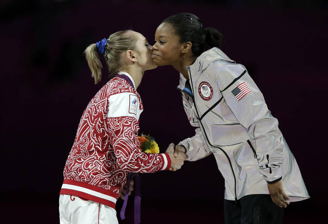 U.S. gymnast and gold medallist Gabrielle Douglas, right, and Russian gymnast and silver medallist Victoria Komova greet each other during the artistic gymnastics women's individual all-around competition at the 2012 Summer Olympics, Thursday, Aug. 2, 2012, in London. (AP Photo/Gregory Bull)