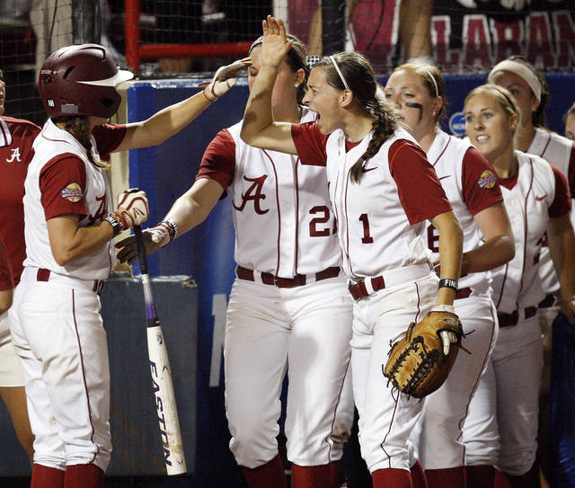 Alabama's Kayla Braud, front right, celebrates with Jennifer Fenton, left, after Fenton scored in the fifth inning during Game 3 of the Women's College World Series against OU at ASA Hall of Fame Stadium on Wednesday. After a lengthy rain delay, the Crimson Tide went on win the national championship 5-4.  Photo by Nate Billings, The Oklahoman
