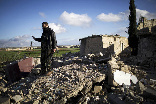 A Free Syrian Army fighter walks over the ruins of a building bombed by a Syrian Army jet in Fafeen village, north of Aleppo province, Syria, Tuesday, Dec. 11, 2012. Syrian rebels including Islamic extremists took full control of a sprawling military base Tuesday after a bloody two-day battle that killed dozens of soldiers, activists said. It was the latest gain by opposition forces bolstered by an al-Qaida-linked group that has provided skilled fighters but raised concerns in the West. (AP Photo/Manu Brabo) ORG XMIT: CAI112