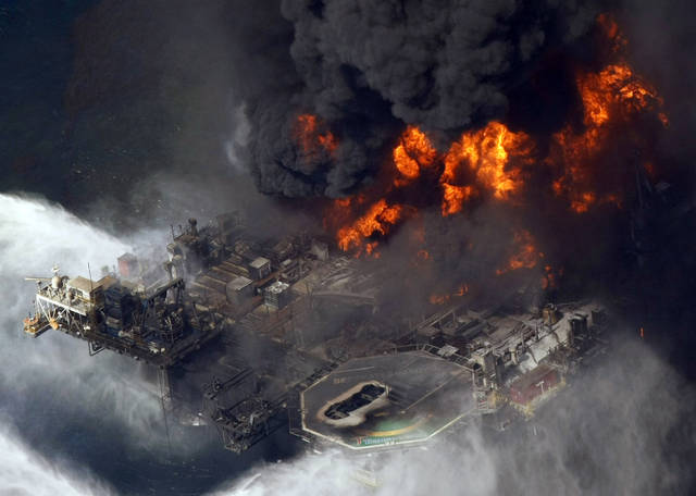 FILE - In this April 21, 2010 file aerial photo, the Deepwater Horizon oil rig burns in the Gulf of Mexico. The Justice Department has reached a $1.4 billion settlement with Transocean Ltd., the owner of the drilling rig that sank after an explosion killed 11 workers and spawned the massive 2010 oil spill in the gulf. On Thursday, Jan. 3, 2013, two people with knowledge of the negotiations say Switzerland-based Transocean would pay the money to resolve the department's civil and criminal probe of the company's role in the Deepwater Horizon disaster. (AP Photo/Gerald Herbert, File)