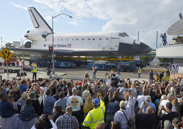 Spectators take pictures of the space shuttle Endeavour as it slowly moves along streets Friday in Los Angeles, where it will become a museum exhibit.  AP photo