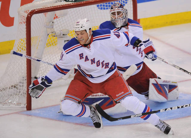 A puck grazes the hand of New York Rangers' Stu Bickel as he defends in front of Henrik Lundqvist as they take on the Ottawa Senators during the second period of game three of first round NHL Stanley Cup playoff hockey action at the Scotiabank Place in Ottawa on Monday, April 16, 2012. (AP Photo/The Canadian Press, Sean Kilpatrick)