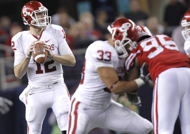 Oklahoma&#039;s Landry Jones (12) looks to pass the ball during the Big 12 football championship game between the University of Oklahoma Sooners (OU) and the University of Nebraska Cornhuskers (NU) at Cowboys Stadium on Saturday, Dec. 4, 2010, in Arlington, Texas.  Photo by Chris Landsberger, The Oklahoman 