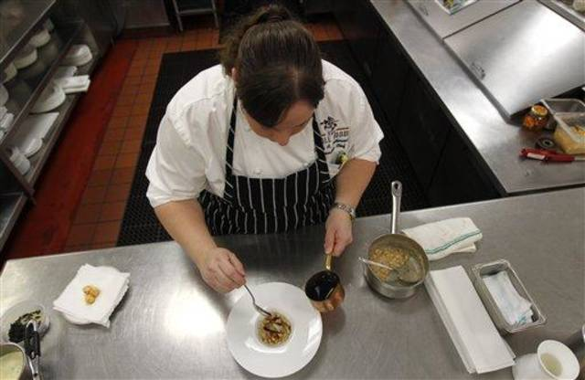 In this Dec. 7, 2012 photo, executive chef Kristin Butterworth prepares her braised pork belly with gulf shrimp, white bean cassoulet, garlic jus and fried baby sage, at the Grill Room of the Windsor Court Hotel in New Orleans. Roughly 50 restaurants in New Orleans are reviving an old Creole custom called reveillon, which stems from the old French tradition of eating a lavish meal after midnight Mass on Christmas Eve. (AP Photo/Gerald Herbert)