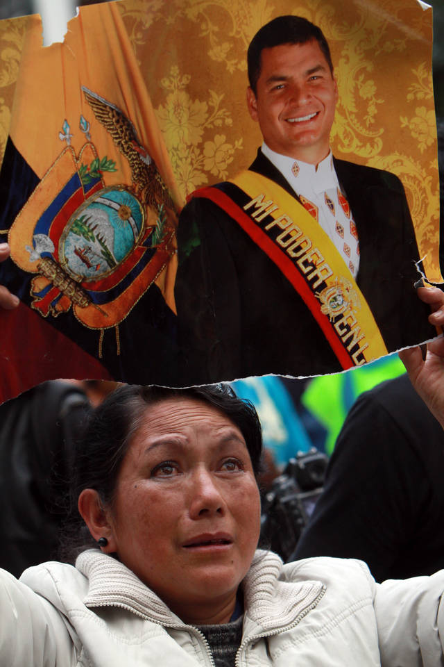 A woman holds up an image of Ecuador's President and candidate for re-election Rafael Correa after presidential elections in Quito, Ecuador, Sunday, Feb. 17, 2013. Although official results had still not been released, Correa celebrated his second re-election as Ecuador's president after an exit poll showed him leading by a wide margin. (AP Photo/Martin Jaramillo)
