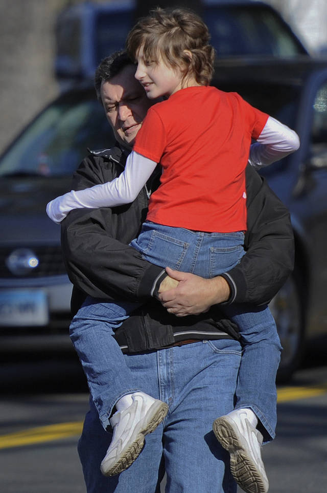 A man carries a child away from the area of a shooting at the Sandy Hook Elementary School in Newtown, Conn., about 60 miles (96 kilometers) northeast of New York City, Friday, Dec. 14, 2012.  A man opened fire Friday inside two classrooms at the school where his mother worked as a teacher, killing 26 people, including 20 children.  The killer, armed with two handguns, committed suicide at the school and another person was found dead at a second scene, bringing the toll to 28, authorities said. A law enforcement official identified the gunman as 20-year-old Adam Lanza.  (AP Photo/Jessica Hill) ORG XMIT: CTJH115