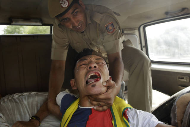 A lone Tibetan protestor who tried to stage a protest against the visit of Chinese Premier Li Keqiang outside the Chinese embassy, is taken away by Indian police in New Delhi, India, Sunday, May 19, 2013. Just weeks after a tense border standoff, China's new premier headed to India on Sunday for his first foreign trip as the neighboring giants look to speed up efforts to settle a decades-old boundary dispute and boost economic ties.(AP Photo/Tsering Topgyal)