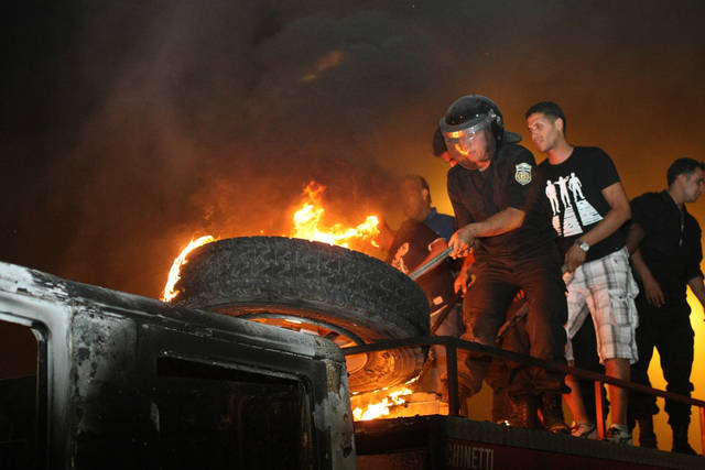 A Tunisian firefighter tries to extinguish a burning tyre on top of a truck after it was set on fire by radical Islamists protesters during overnight riots in Sijoumi near Tunis, Tuesday, May 12, 2012. Tunisian police fired warning shots to disperse radical Islamist protesters after they set a security post ablaze and ransacked an art exhibit they called offensive to Islam. (AP Photo/Amine Landoulsi)