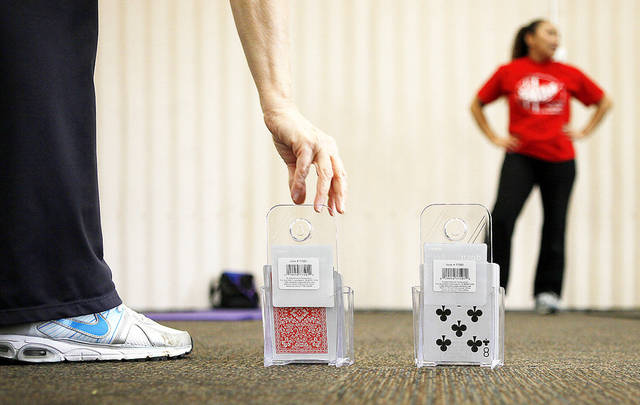 Instructor Robin Barlow reaches for a playing card during a Move Into Fitness class in Moore on Thursday. The cards were used to randomize the exercises in the class. The city has increased the number of fitness and nutrition classes it offers. PHOTOS BY BRYAN TERRY, THE OKLAHOMAN
