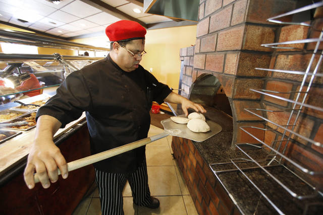 Chef Nordeen Bennai prepares pita dough for a trip in the oven at Capers Mediterranean Buffet and Bistro. <strong>STEVE GOOCH - THE OKLAHOMAN</strong>