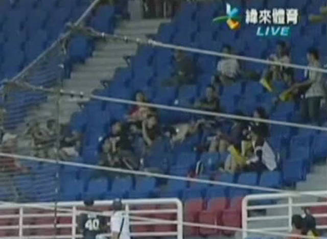 In this Sept. 24, 2011 image taken from Chinese Professional Baseball League video, a Taiwanese fan, center, identified only as Bai, reaches out to catch a foul ball while dropping his daughter into seats below at a Taoyuan baseball park, Taiwan, during a game between Taipei's Brother Elephants team and Taoyuan's Lamigo Monkeys. The girl, who was not named, said later one leg was slightly hurt. (AP Photo/Chinese Professional Baseball League) MANDATORY CREDIT NO SALES