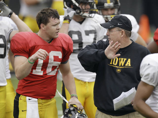 FILE- In this April 14, 2012, filephoto, Iowa quarterback James Vandenberg talks with new offensive coordinator Greg Davis, right, during Iowa's annual NCAA college football spring scrimmage in Iowa City, Iowa. Vandenberg was supposed to be the player the Hawkeyes could lean on early while they adjusted to Davis's new system. But Vandenberg averaged less than four yards per attempt in Saturday's narrow win over Northern Illinois, and running back Damon Bullock had to bail Iowa out with a late TD run. (AP Photo/Charlie Neibergall, File)