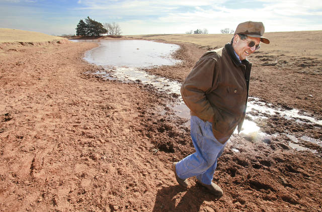 John Pfeiffer, of Pfeiffer Angus Farms, walks across a dried up part of one of his ponds on his ranch near Orlando, Okla., Wednesday, December 15, 2010. Photo by David McDaniel, The Oklahoman