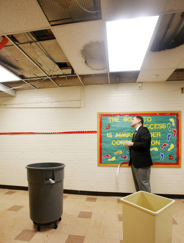 Wastebaskets collect water dripping from the ceiling as Oklahoma City Public Schools Superintendent Karl Springer looks at damage to ceiling tiles at Monroe Elementary School in Oklahoma City Wednesday, Jan. 25, 2012. Rain water leaked through the ceiling as thunderstorms moved through the metro area overnight. Photo by Paul B. Southerland, The Oklahoman