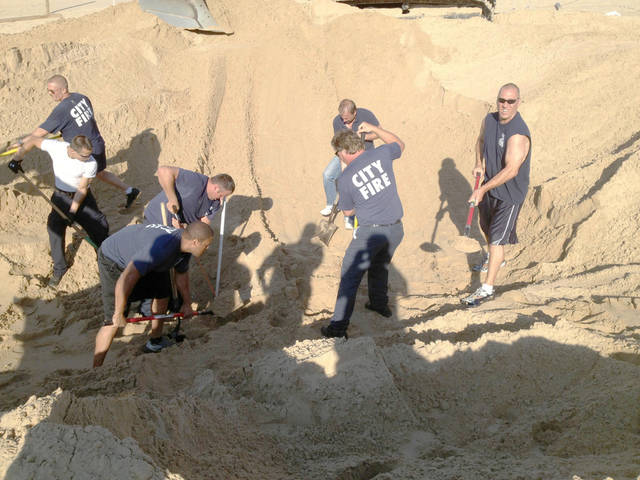 FILE - In this Juy 12, 2013, file photo Michigan City police and firefighters dig with shovels to rescue Nathan Woessner, of Sterling, Ill., who was trapped for over three hours under about 11 feet of sand at Mount Baldy dune near Michigan City, Ind. The grandfather of a 6-year-old boy says he is responsive and able to move his arms and legs. (AP Photo/Michigan City Fire Department via The News Dispatch)