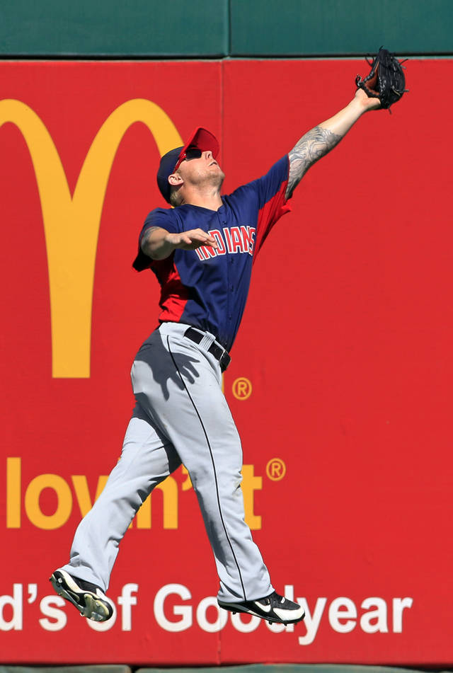 Cleveland Indians right fielder Aaron Cunningham makes a leaping catch to rob Cincinnati Reds' Drew Stubbs of a hit in the fourth inning of a spring training baseball game on Friday, March 30, 2012, in Goodyear, Ariz. (AP Photo/Mark Duncan)