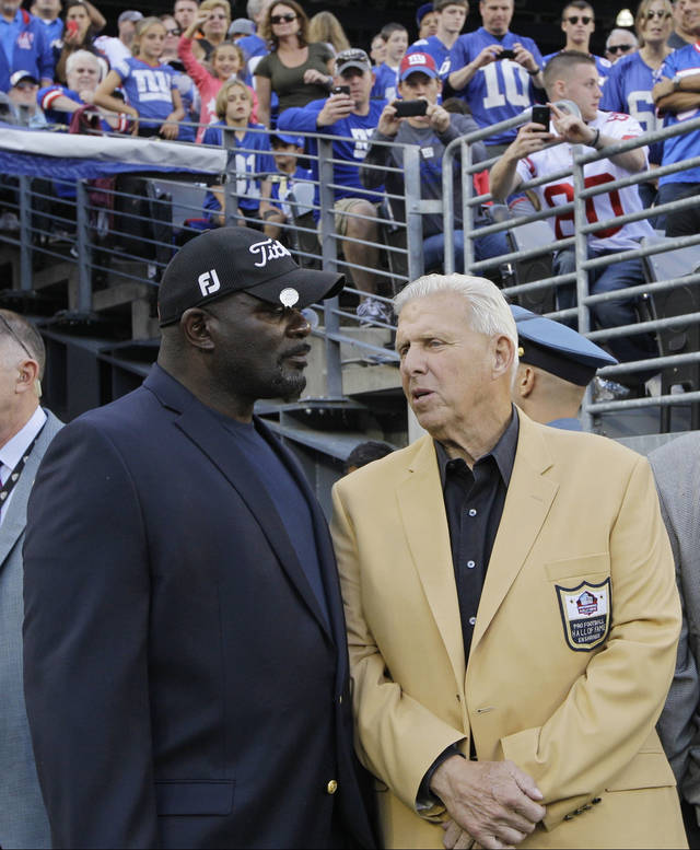 Lawrence Taylor, left, and Bill Parcells, center, talk during the first half of an NFL football game between the New York Giants and the Denver Broncos Sunday, Sept. 15, 2013, in East Rutherford, N.J. (AP Photo/Kathy Willens)