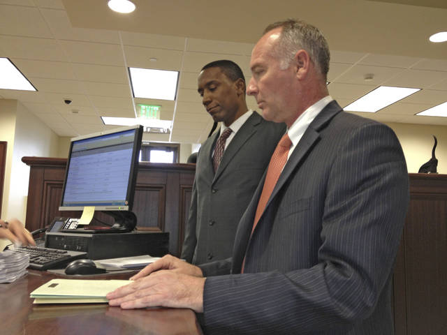 Attorney David Slane, front, files a petition Monday asking the state Court of Criminal Appeals to dismiss a case against Tyrone Nash, back. Nash is accused of raping a 16-year-old student who attended school where he taught. PHOTO BY TIM WILLERT, THE OKLAHOMAN