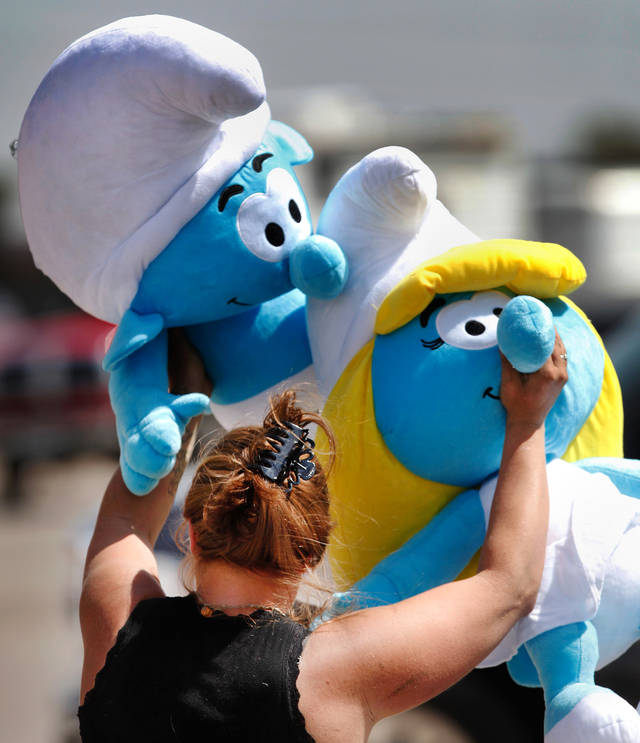 Carnival employee Heather Farnham carries two large Smurfs after retrieving them from a pile of plush stuffed toys. The toys will be used as prizes at this booth, which challenges players to toss balls into colored goblets. Midway and carnival workers were busy most of Tuesday assembling game booths and rides and washing and cleaning tarps and tents.