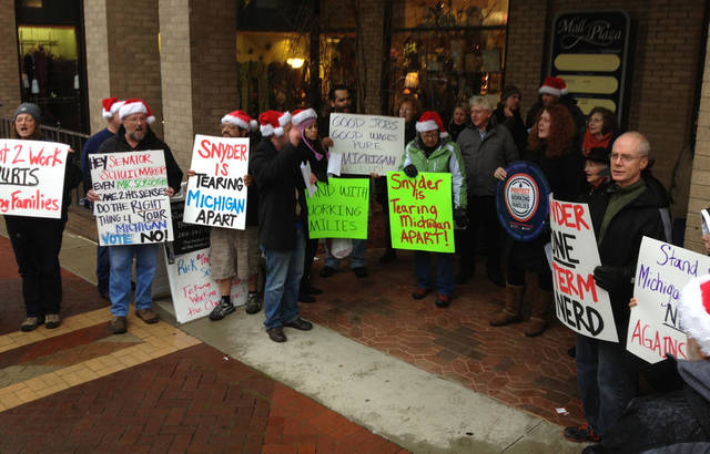 Dozens of union backers protest against the right-to-work bills outside Sen. Tonya Schuitmaker's Kalamazoo, Mich., office Sunday, Dec. 9, 2012. People sang Christmas-themed protest songs and carried picket signs outside the office of the Republican state senator, who received a bag of coal from union-rights demonstrators protesting her vote to make Michigan a right-to-work state. (AP Photo/The Kalamazoo Gazette, Aaron Mueller) ALL LOCAL TV OUT; LOCAL TV INTERNET OUT