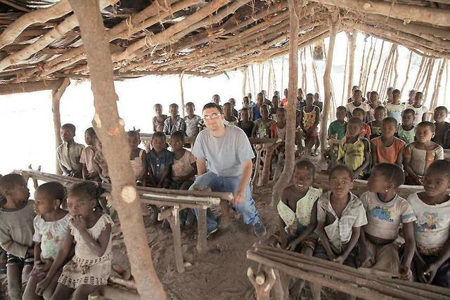 1040i?s media specialist Jacob Meyer, center, sits with a group of Ivory Coast children in a makeshift school, far away from the country?s bigger cities. PHOTO PROVIDED