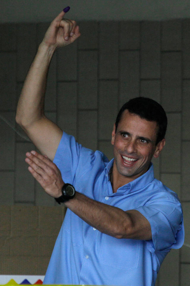 Miranda's  Gov. Henrique Capriles shows his finger marked after casting his ballot at a polling station in Caracas, Venezuela, Sunday, Dec. 16, 2012. Venezuelans are choosing governors and state lawmakers  in elections that have become a key test of whether President Hugo Chavez's movement can endure if the socialist leader leaves the political stage. (AP Photo/Fernando Llano)