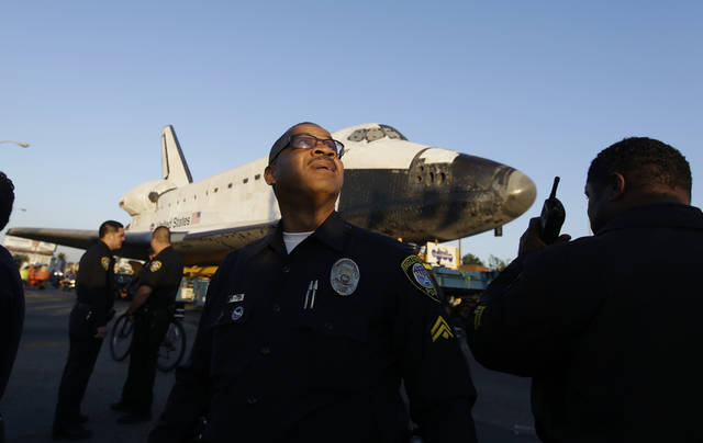 Law enforcement personnel direct traffic as the space shuttle Endeavour makes it's way down Manchester Blvd. to a public viewing at Forum in Inglewood, Calif., Saturday, Oct. 13, 2012. Endeavour's 12-mile road trip kicked off shortly before midnight Thursday as it moved from its Los Angeles International Airport hangar en route to the California Science Center, its ultimate destination. (AP Photo/Chris Carlson)