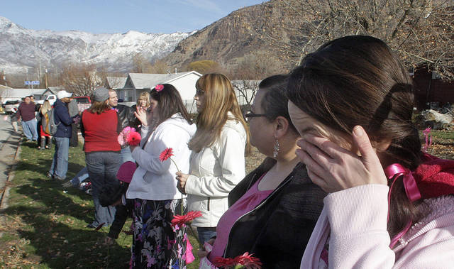 Mournier Claudia Wardle cries after the hearse carrying Emilie Parker passed by following funeral services for the 6-year old Connecticut elementary shooting victim, Saturday, Dec. 22, 2012, in Ogden, Utah.  Emilie, whose family has Ogden roots, was one of 20 children and six adult victims killed in a Dec. 14 mass shooting at Sandy Hook Elementary in Newtown, Conn.  (AP Photo/Rick Bowmer) ORG XMIT: UTRB110