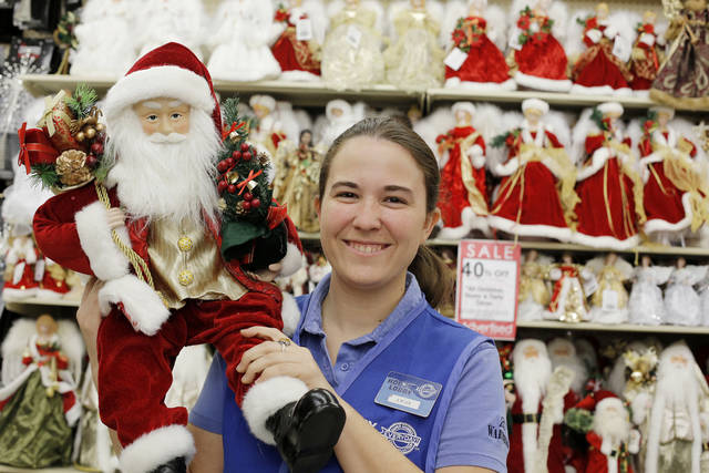 Hobby Lobby worker Lydia Wells shows off just one of the many Santas at Hobby Lobby, 3160 S Broadway in Edmond. <strong>DOUG HOKE - THE OKLAHOMAN</strong>