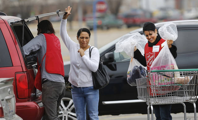 "Jesse Snyder of Midwest City puts bags into a woman's vehicle as she holds the door open for him. Stephanie Condeluci of Edmond, unloads additional bags of toys and gifts from a shopping cart. This is Snyder's first year to volunteer at the event. He said it was ""fun"" and also described it as ""rewarding."". Condeluci volunteered with other employees from  Feed the Children. She said this is her first year to help, but added, ""it won't be my last.""  She said helping people with their toys and bicycles is ""better than Christmas at your own home. So many people don't have what we have.""  She said she cried after assisting some of the first clients, but those tears were soon replaced with a big smile for people she was helping. The Salvation Army and Feed the Children teamed to distribute bicycles and toys for children,  and handed out boxes of food for families at their annual distribution event Wednesday, Dec. 19, 2012. Salvation Army officials said 100 volunteers helped make the event go smoothly. The volunteers loaded bags of toys and bikes into vehicles of clients who had been pre-approved for assistance.  Many of the gifts were provided through the Salvation Army's Angel Tree program   Photo by Jim Beckel, The Oklahoman"