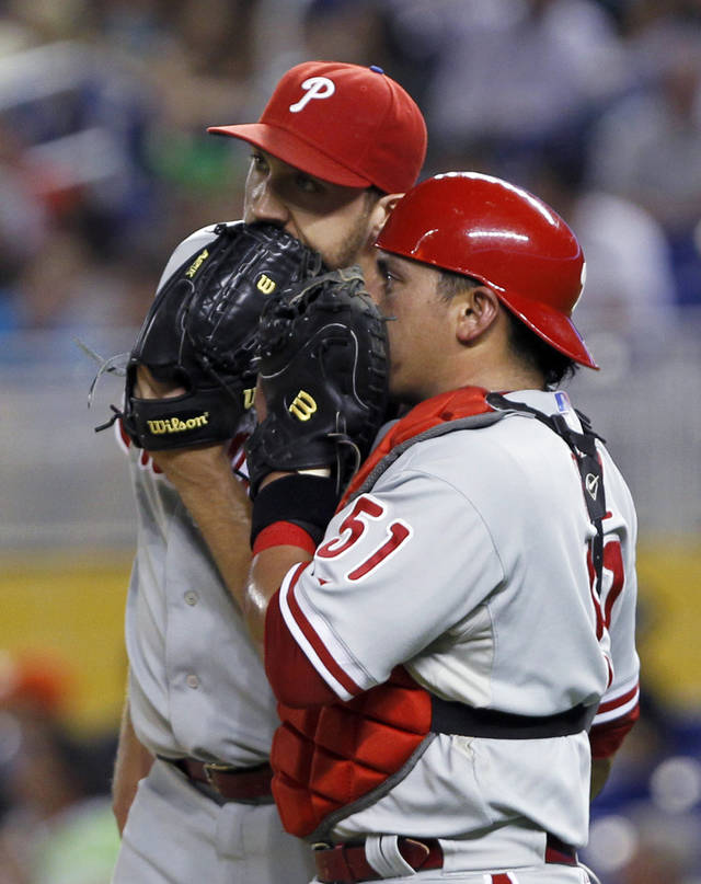 Philadelphia Phillies catcher Carlos Ruiz (51) talks to relief pitcher Josh Lindblom after Miami Marlins' Bryan Petersen hit a double in the ninth inning of a baseball game in Miami, Friday, Sept. 28, 2012. The Marlins won 2-1. (AP Photo/Alan Diaz)