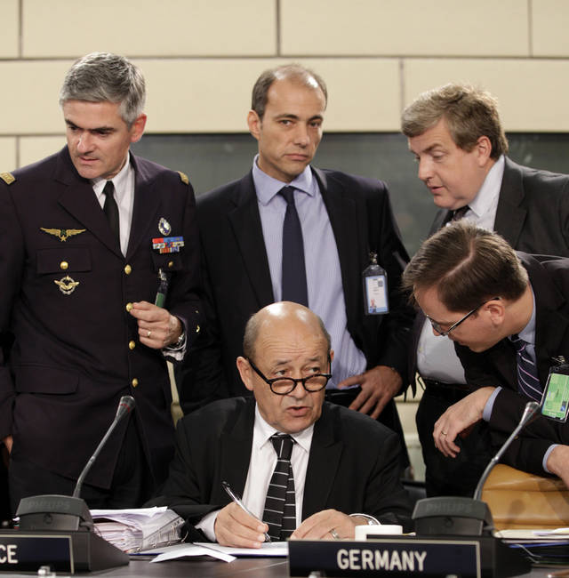 French Defense Minister Jean-Yves Le Drian, center, speaks with members of his delegation during a meeting of NATO Defense Ministers at NATO headquarters in Brussels on Tuesday, Oct. 9, 2012. NATO defense leaders gathering for a two-day meeting in Brussels, are committed to the war in Afghanistan, according to U.S. and alliance officials, but there are growing signs that the Afghan political and military hostilities against the coalition are starting to wear on the coalition. (AP Photo/Virginia Mayo)