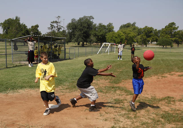 Chance Johnson (left), 11, runs into home during a kickball tournament hosted by the Oklahoma City Police Department at South Rotary Park in Oklahoma City, Wednesday, June 27, 2012.  Photo by Garett Fisbeck, The Oklahoman