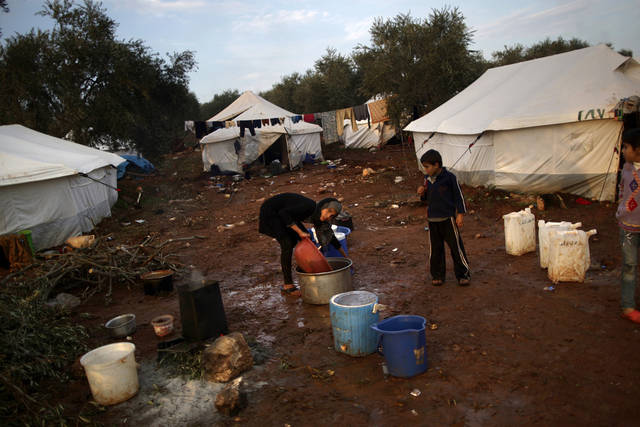 A Syrian girl, who fled her home with her family in Idlib, collects water at a camp for displaced Syrians in the village of Atmeh, Syria, Thursday, Dec. 13, 2012. (AP Photo/Muhammed Muheisen) ORG XMIT: XMM102