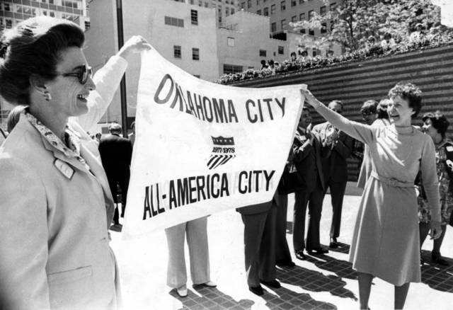 """Mrs. Jackie Carey, left, and Mayor Patience Latting display a flag denoting the city's All-American City status"" during announcement ceremonies in Kerr-McGee Plaza in downtown Oklahoma City. Staff photo by Jim Argo taken 4/13/78; photo ran in the 4/14/78 Daily Oklahoman."