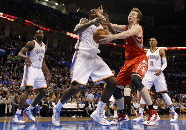 Oklahoma City 's Kendrick Perkins (5) and Houston's Omer Asik (3) battle for a loose ball during the NBA basketball game between the Houston Rockets and the Oklahoma City Thunder at the Chesapeake Energy Arena on Wednesday, Nov. 28, 2012, in Oklahoma City, Okla.   Photo by Chris Landsberger, The Oklahoman