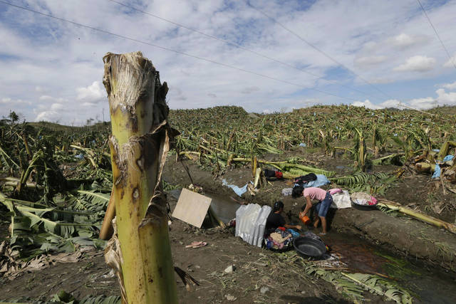 Residents wash their clothes amid the devastation left by Typhoon Bopha, in the village of Andap, New Bataan township, Compostela Valley in southern Philippines Wednesday, Dec. 5, 2012. Typhoon Bopha, one of the strongest typhoons to hit the Philippines this year, barreled across the country's south on Tuesday, killing scores of people while triggering landslides, flooding and cutting off power in two entire provinces. (AP Photo/Bullit Marquez)