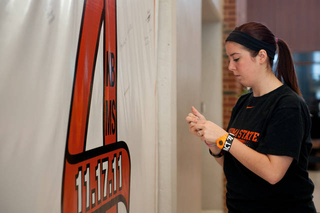 "Taylor Miller writes on the ""Remember the 4"" banner Friday in Gallagher-Iba Arena in Stillwater. Saturday is the first anniversary of the airplane crash that killed two Oklahoma State University women's basketball coaches and two OSU supporters. Photo by Mitchell Alcala for The Okahoman <strong>Mitchell Alcala - Mitchell Alcala for the Oklahoma</strong>"