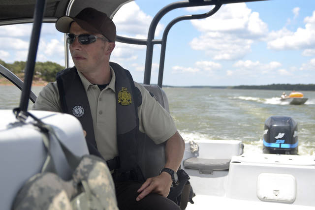 Oklahoma Highway Patrol trooper Danny Proctor leads a boat into a cove while on patrol on Sunday at Lake Thunderbird. PHOTO BY ADAM KEMP, THE OKLAHOMAN