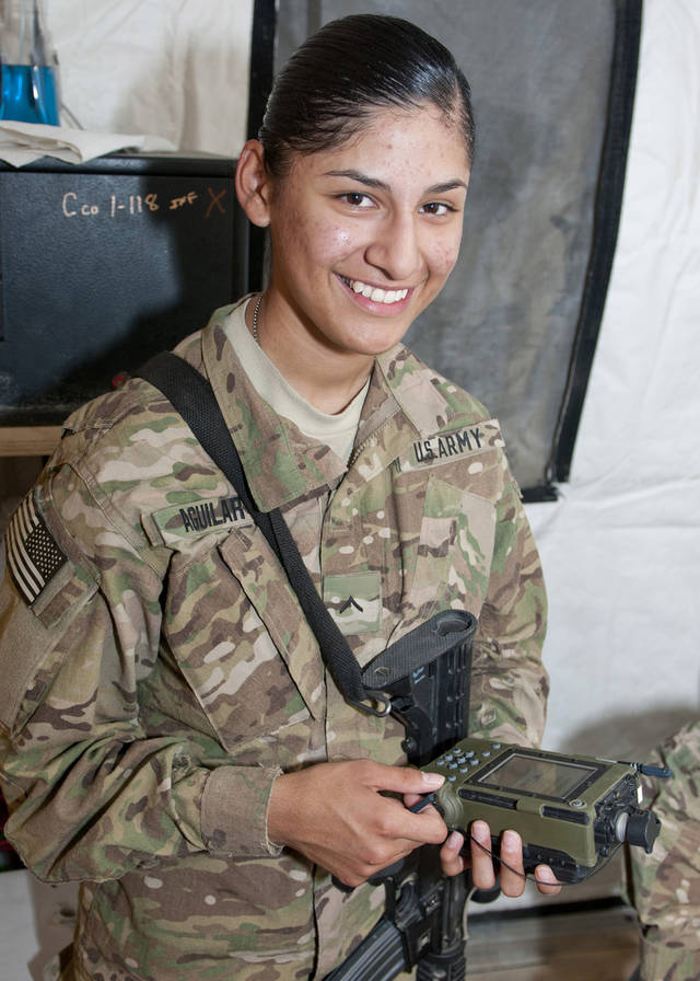MILITARY: Pvt. Raquel Aguilar of Oklahoma City, Okla., with Headquarters, Headquarters Company, 45th Infantry Brigade Combat Team smiles for the camera as she works with a Simple Key Loader July 16, at Forward Operating Base Gamberi, Afghanistan. Aguilar works in the communications section, and is on her first deployment. (Photo by Spc. Leslie Goble, Task Force Thunderbird Public Affairs Office)