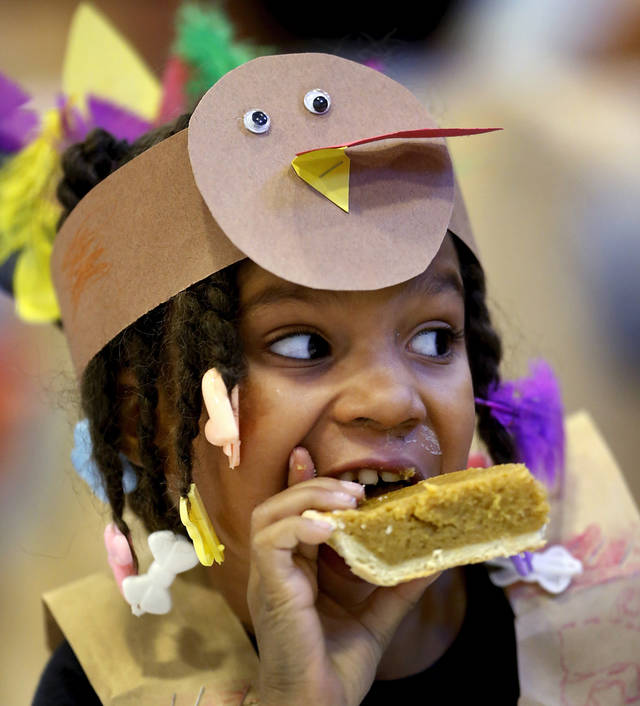 Cynih (cq) Robins (cq) bites into her pie. Kindergarten students at Eugene Field Elementary School in Oklahoma City have been learning about Thanksgiving traditions and  the history of the national  holiday in America.  Their teachers helped them make paper sack vests and turkey head pieces to wear.  To celebrate the end of the Thanksgiving lesson and reward the students for working so hard, about 80 students in the four kindergarten classes held a pumpkin pie break in the cafeteria Tuesday afternoon, Nov. 20, 2012. The students dressed in their creative paper sack turkey vests and head dresses.   Photo by Jim Beckel, The Oklahoman