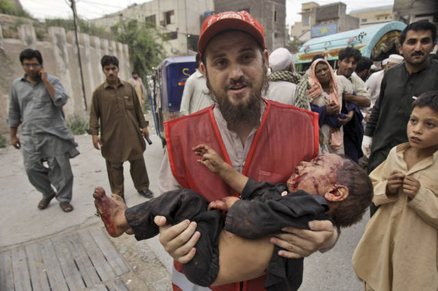 A Pakistani rescue worker carries a child, who was injured in an explosion in a Sunni shrine, to a hospital in Peshawar, Pakistan, Thursday, June 21, 2012. A Pakistani police officer said that two children were killed by the explosion at the shrine as dozens of people gathered there.(AP Photo/Mohammad Sajjad)