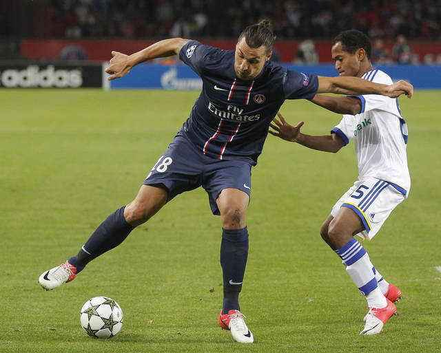 Paris Saint Germain's Swedish player Zlatan Ibrahimovic, left, dribbles past Dynamo Kiev's Brazilian Raffael, right, during a group A Champions League round, first leg, soccer match at Parc des Princes stadium in Paris, Tuesday, Sept. 18, 2012. Paris Saint Germain won 4-1.(AP Photo/Michel Euler)