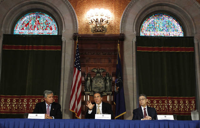 New York Gov. Andrew Cuomo, center, speaks during a news conference in the Red Room at the Capitol as Senate Majority Leader Dean Skelos, R-Rockville Center, left, and Assembly Speaker Sheldon Silver, D-Manhattan, listen in Albany, N.Y., on Tuesday, May 22, 2012. Cuomo says a new, temporary board set to run the New York Racing Association will enhance racing while working on the state's expansion of gambling. (AP Photo/Mike Groll)