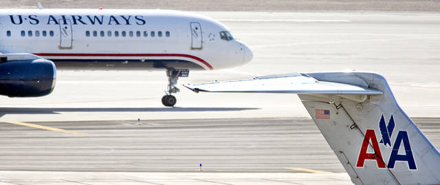 In this Feb. 7, 2013, photo, a US Airways jet taxis past an American Airlines jet parked at the gate at Sky Harbor International Airport, in Phoenix.  Directors of American Airlines and US Airways reportedly plan to meet Wednesday to consider a merger. The Wall Street Journal reported Monday, Feb. 11, 2013, that negotiators were still considering the makeup of the combined company's board and an exact role for the CEO of American parent AMR Corp.  (AP Photo/The Arizona Republic,Tom Tinkle )  MARICOPA COUNTY OUT; MAGS OUT; NO SALES