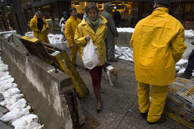 A pedestrian walks her dog through a working crew as they stack sandbags beside concrete barriers to protect buildings near the World Financial Center in anticipation of massive flooding, Monday, Oct. 29, 2012, in New York. Hurricane Sandy bore down on the Eastern Seaboard's largest cities Monday, forcing the shutdown of mass transit, schools and financial markets, sending coastal residents fleeing, and threatening a dangerous mix of high winds, soaking rain and a seawater surge of anywhere from 6 to 11 feet. (AP Photo/ John Minchillo) ORG XMIT: NYJM104