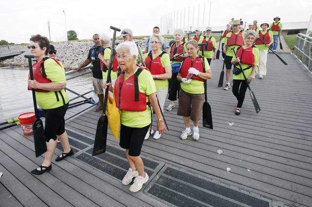 Senior citizens from Spanish Cove Retirement Village head to the dock with their paddles to go dragon boating on the Oklahoma River in Oklahoma City Thursday, Aug. 16, 2012.  Photo by Paul B. Southerland, The Oklahoman <strong>PAUL B. SOUTHERLAND - PAUL B. SOUTHERLAND</strong>