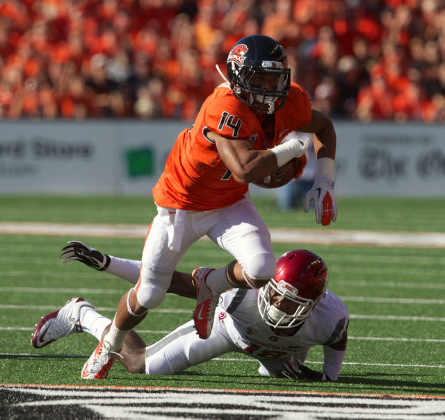 Oregon State cornerback Jordan Poyer (14) makes one of his three interceptions against Washington State during their NCAA college football game in Corvallis, Ore., Saturday, Oct 6, 2012. Oregon State won 19-6. (AP Photo/The Oregonian, Doug Beghtel)
