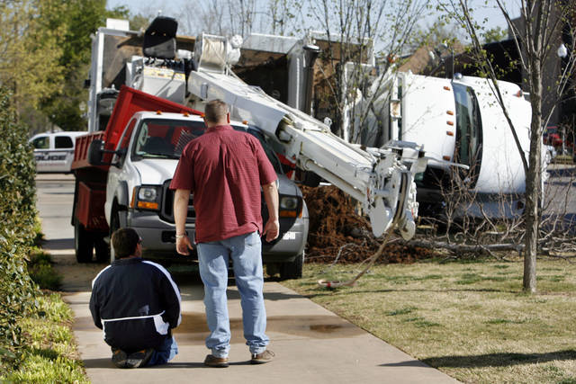 An injured man (kneeling left) waits for assistance after a crane removing a tree at Boyd House, home of University of Oklahoma president David Boren, toppled onto a flatbed truck in Norman, Okla. on Wednesday, April 8, 2009.      Photo by Steve Sisney, The Oklahoman